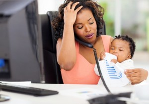 stressed african american businesswoman in office holding her little girl while talking on telephone